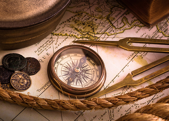 Vintage compass lies on an medieval map